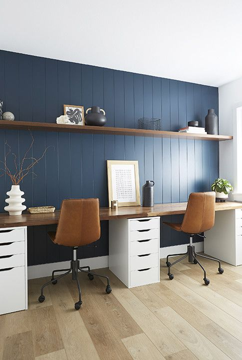 a stylish home office with a navy planked wall, a floating shelf and a double desk with a stained desktop, leather chairs and some pretty vases