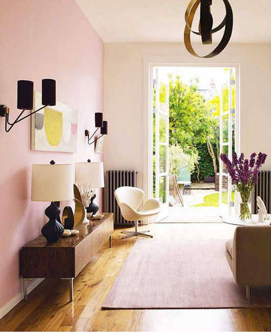 a stylish living room with a pink accent wall, some chic furniture in modern style, a catchy chandelier and black sconces