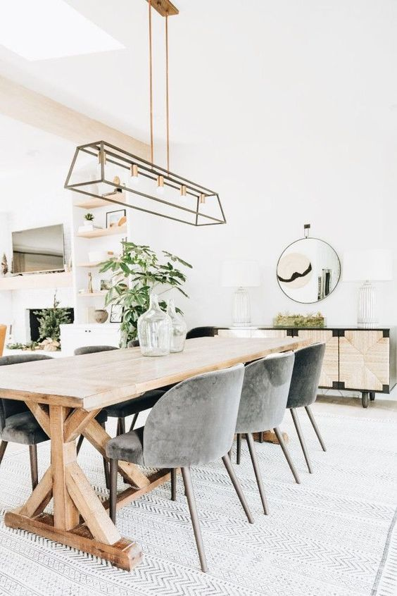 a stylish modern country dining room with a trestl table, grey chairs, a metal chandelier, an inlaid console and a round mirror