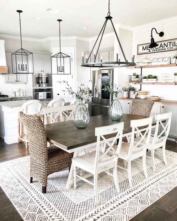a stylish modern country dining space with a stained table, woven and wooden chairs, a metal chandelier and a buffet at the wall