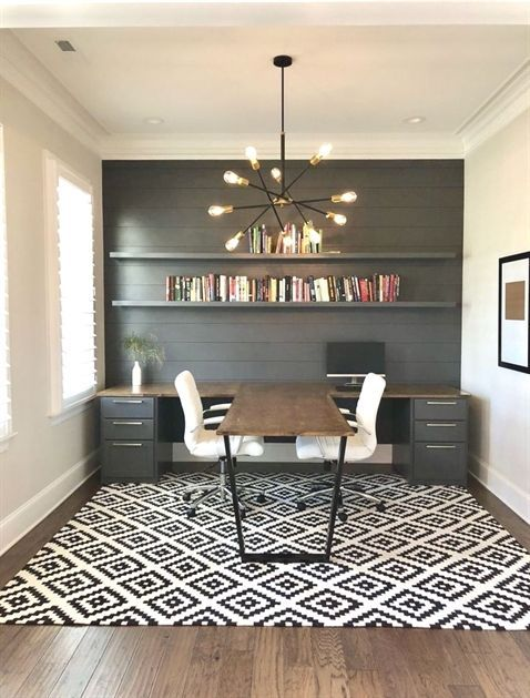 a stylish modern country home office with a grey planked wlal and a unique double desk with an additional center desktop for workign together