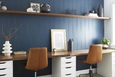 a stylish modern country home office with a navy planked accent wall, a shared desk, leather chairs, a long floating shelf for storage