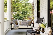 a stylish modern farmhouse porch with a black suspended daybed with pillows, black wooden rockers, a striped rug and some blooms
