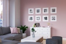 a stylish modern living room with a pale pink accent wall and a grid gallery wall, a white sideboard, a grey sectional, a low white coffee table