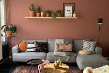 a stylish modern living room with a pink accent wall, a grey sectional, a printed boho rug, a shelf with lots of potted plants and an arrangement of side tables