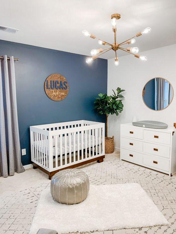 a stylish modern nursery with a blue wall