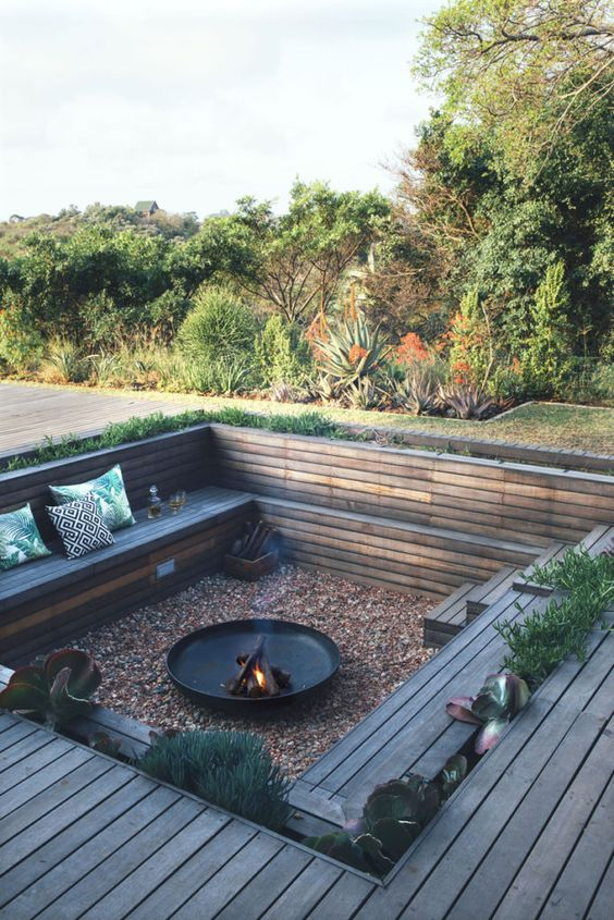 a sunken conversation pit with gravel on the ground, a fire pit, built-in wooden benches around and some growing greenery
