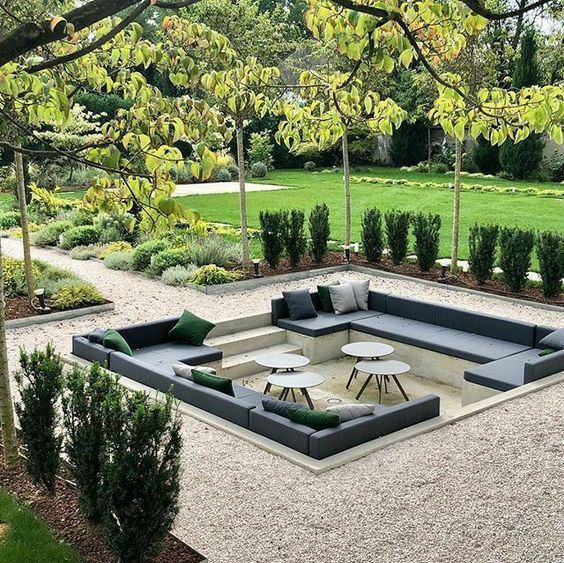 a sunken outdoor living room with built-in benches, several coffee tables is a lovely space to receive guests
