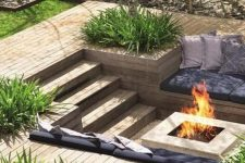 a sunken patio with a deck, a fire pit, built-in benches with pillows and grasses growing around is a very lovely space