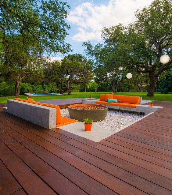 a sunken patio with a rich stained wooden deck, a fire pit, upholstered benches around it and a lovely scenery to admire while staying here