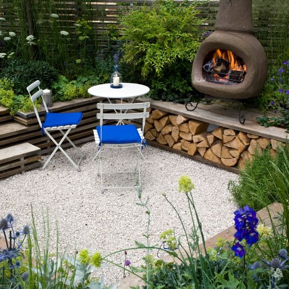 a sunken patio with gravel on the ground, a hearth, a small dining space and lots of greenery and blooms growing around