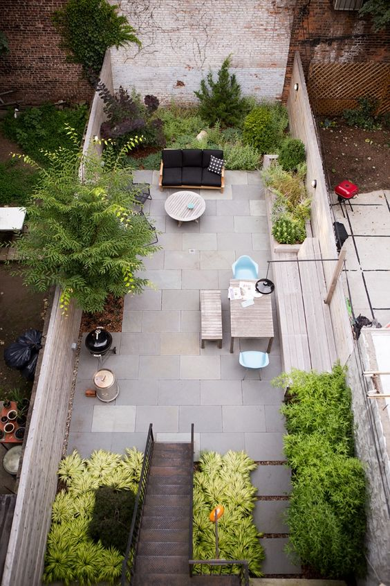 a sunken patio with growing and potted plants, with a living and dining space is very welcoming and stylish