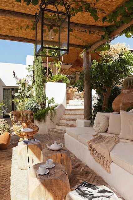 a sunken terrace with a built-in sofa, some wooden and rattan furniture, neutral textiles surrounded with greenery