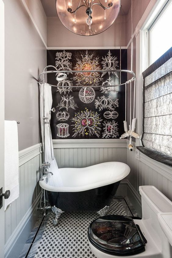 a tiny yet fancy bathroom with a mosaic tile floor, a black painted wall, a black vintage soak tub and a brass chandelier