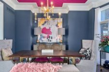 a unique dining room with navy walls and a hot pink ceiling, a wooden table and upholstered chairs, a gold chandelier