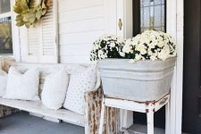 a vintage farmhouse porch with a white bench and printed pillows, a vintage metal sconce, a leaf wreath, potted blooms and pumpkins