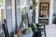 a vintage farmhouse porch with black rockers, a grey chest, potted greenery, a basket, a console and a wreath of wheat