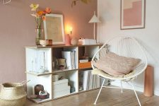 a welcoming Scandinavian nook with an open storage unit, a white chair, some lamps, a pale pink accent wall and a basket