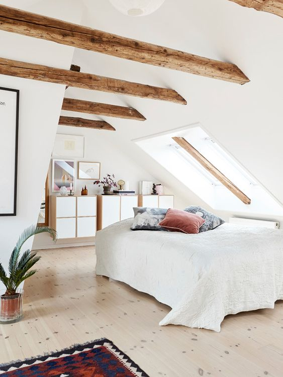 a welcoming attic bedroom with wooden beams, floating dressers and a bed by the skylight, a bright rug and pillows and a potted plant