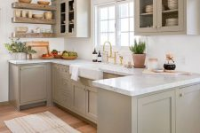 a welcoming dove grey modern country kitchen with shaker style cabinets, white marble countertops, a white tile backsplash and open shelves