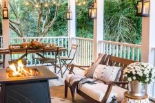 a welcoming farmhouse porch with a fire pit, a dining set, a wooden bench with upholstery, pumpkins and potted blooms in a bucket