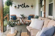 a welcoming farmhouse porch with a large wicker sofa, a chest coffee table, rattan rockers, potted greenery and a vintage chandelier