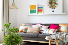 a welcoming living room with a grey sofa, a ledge gallery wall with bright artworks, hot pink accessories and a bold mosaic tile floor