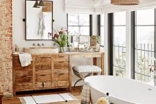 a welcoming modern country bathroom with exposed brick, a stained floor, a stained vanity, a woven lampshade and chic appliances