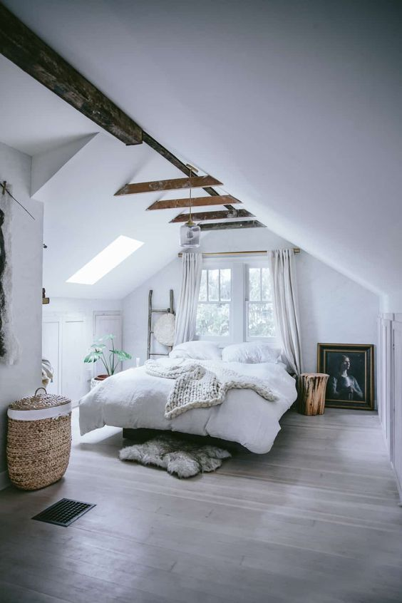 a welcoming modern country bedroom with an attic ceiling and wooden beams, a bed, a window and a skylight, potted plants and a basket