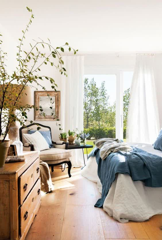 a welcoming modern country bedroom with stained and dark furniture, neutral and blue bedding, a mirror in a frame and potted plants