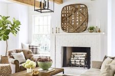 a welcoming modern country living room with a brick clad fireplace, neutral furniture, layered rugs, printed textiles and wooden beams on the ceiling
