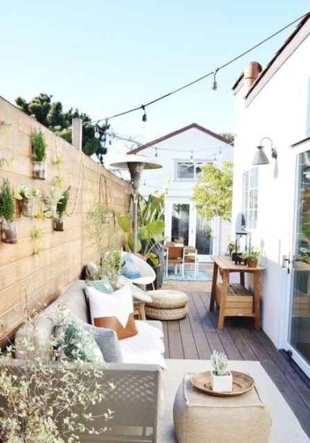 a welcoming modern farmhouse deck with a sofa, some poufs and ottomans, a wooden console and a dining space plus greenery hanging on the wall