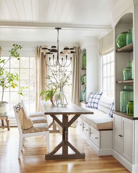 a welcoming rustic dining room with a white planked ceiling, a built-in banquette seating, a trestle table, vintage chairs and a chandelier