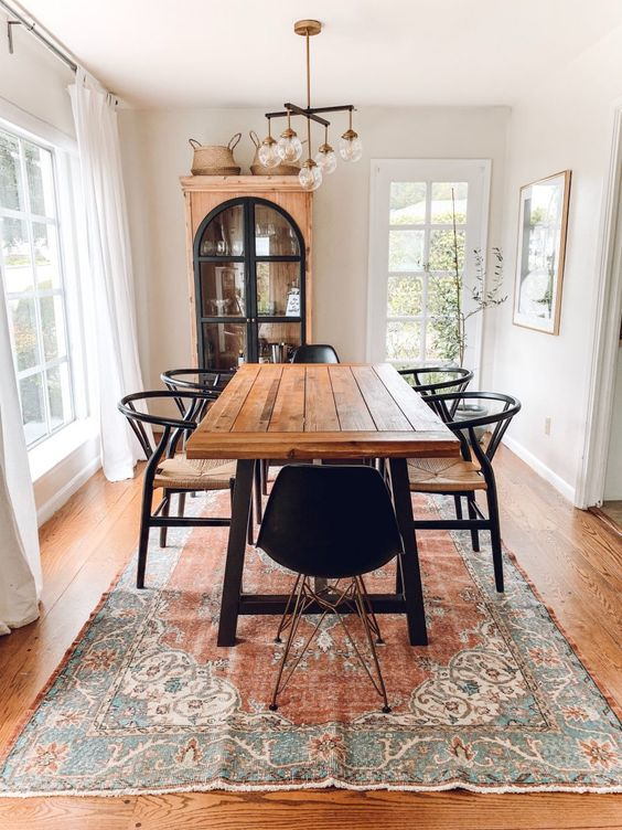 a welcoming rustic dining space with a dining table with a stained tabletop, black woven chairs, a chic chandelier and a vintage buffet