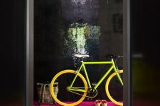 a whimsical entryway with glossy black walls, a hot pink floor, a neon green and yellow bike is amazing