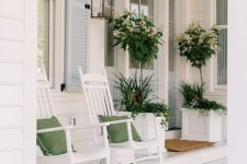 a white farmhouse porch with rockers and green pillows, a side table, a lantern and lots of greenery in large white planters is chic and clean