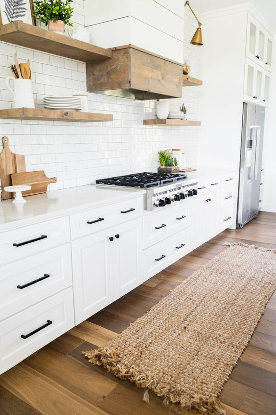 a white modern country kitchen with shaker style cabinets, white stone countertops, wooden floating shelves and a wooden hood