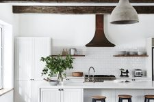 a white modern country kitchen with white planked cabinets, dark ceiling beams, pendant lamps, tall stools and shelves