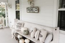 a white vintage farmhouse porch with neutral pillows, pumpkins, lanterns and a bag with firewood is styled for the fall in a lovely way