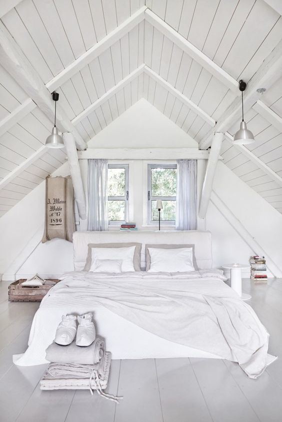 a whitewashed attic bedroom with an upholstered bed, mismatching nightstands, neutral and pastel bedding, pendant lamps