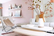 an airy and dreamy living room with a light pink accent wall, chic Scandinavian furniture, low coffee tables, a cool artwork and ledge gallery walls