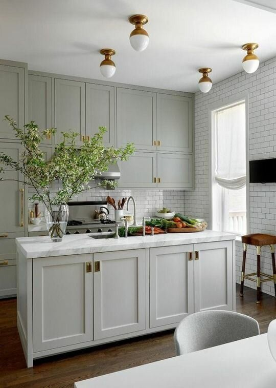 an amazing pale green modern country kitchen with shaker cabients, white subway tiles, brass touches for extra elegance