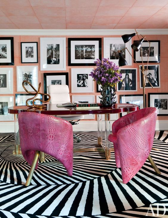 an artistic home office with a pink accent wall fully covered with a black and white gallery wall, a unique desk and hot pink leather chairs on brass legs