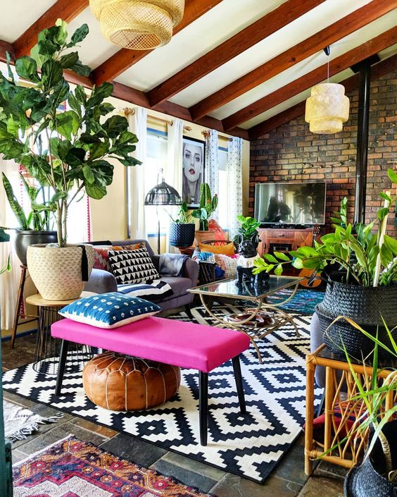 an eclectic attic space with an extended brick wall, wooden beams on the ceiling, a sofa, a hot pink bench and potted plants is cool