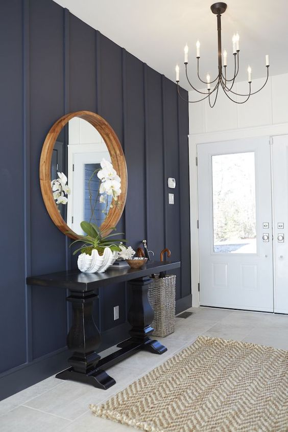 an elegant coastal farmhouse entryway with a navy paneled wall, a tiled floor, a black console table, a round mirror in a wooden frame and a vintage chandelier