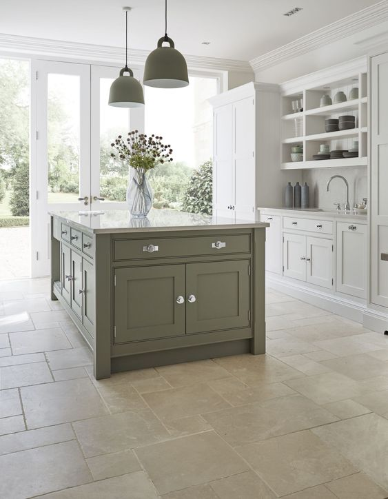an elegant dove grey and green modern country kitchen with green pendant lamps and a stone floor is a chic and welcoming space