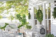 an elegant farmhouse porch with white wicker furniture, striped textiles, potted greenery and evergreens is very welcoming