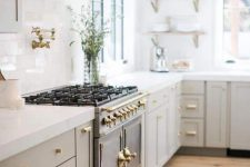 an elegant light grey modern country kitchen with white stone countertops, a vintage cooker and a chic hood plus open shelves