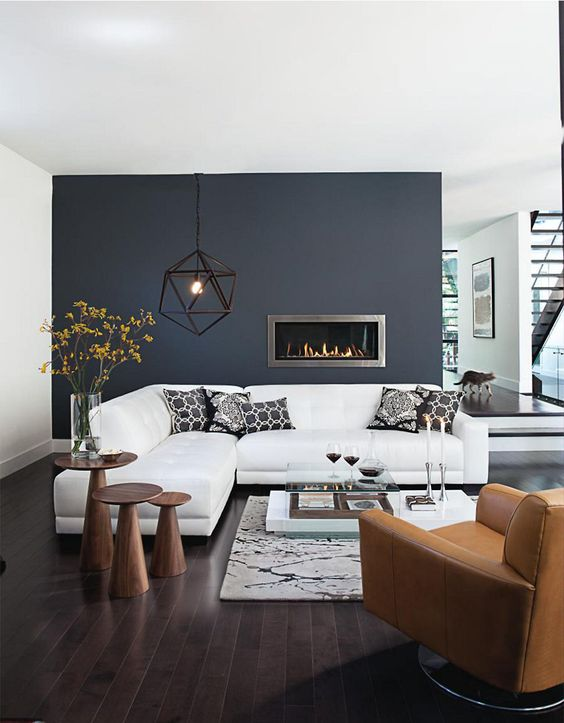 an elegant living room with a navy accent wall, a white corner sofa, a tan leather chair and an arrangement of wooden side tables plus a built-in fireplace