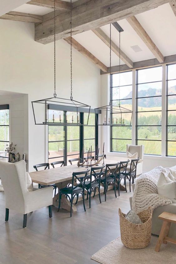 an elegant modern country dining space with lots of windows for the views, a stained table, black and white chairs and vintage chandeliers